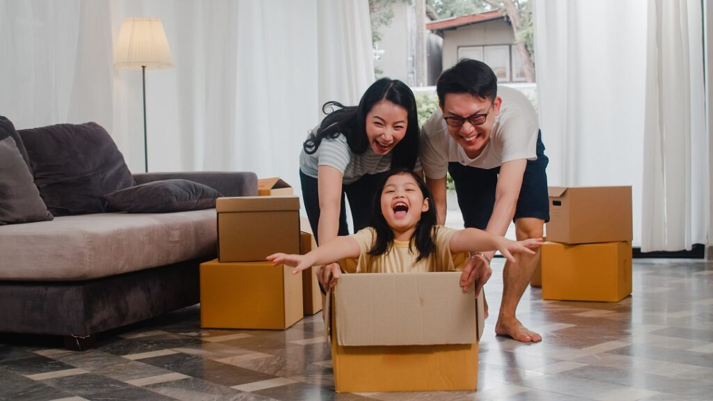 Happy Asian young family having fun laughing moving into new home